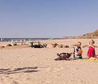 Familie op strand bij vakantiehuis in Denemarken